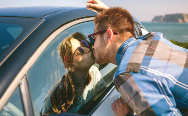 Young couple kissing through the glass Young couple kissing through the glass of the car outdoors pecking stock pictures, royalty-free photos & images