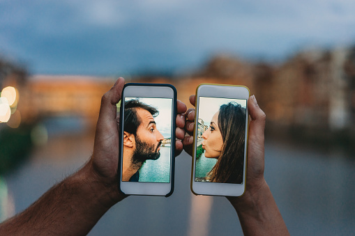 Young couple kissing via a mobile phone - Social distancing concept. During the Covid-19 Coronavirus quarantine it is important to keep a safe distance.