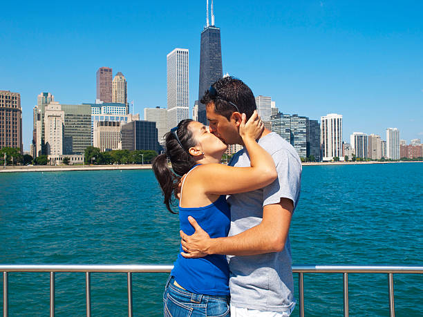 Young couple kissing with the Chicago skyline at background stock photo