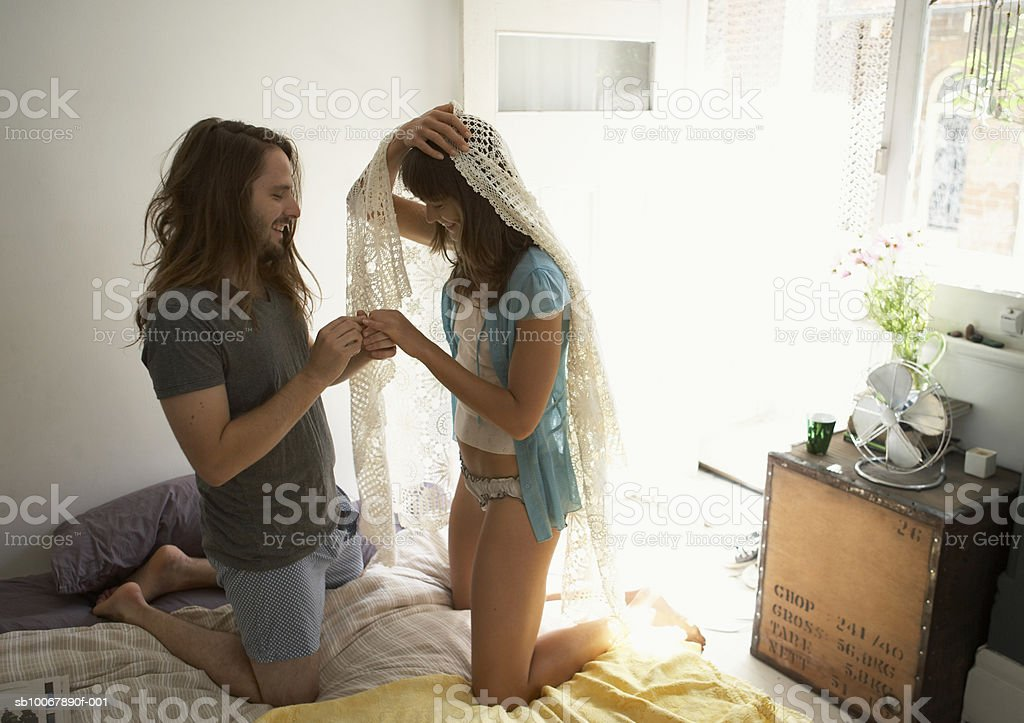 Young couple kneeling on bed, holding hands, side view royalty-free stock photo