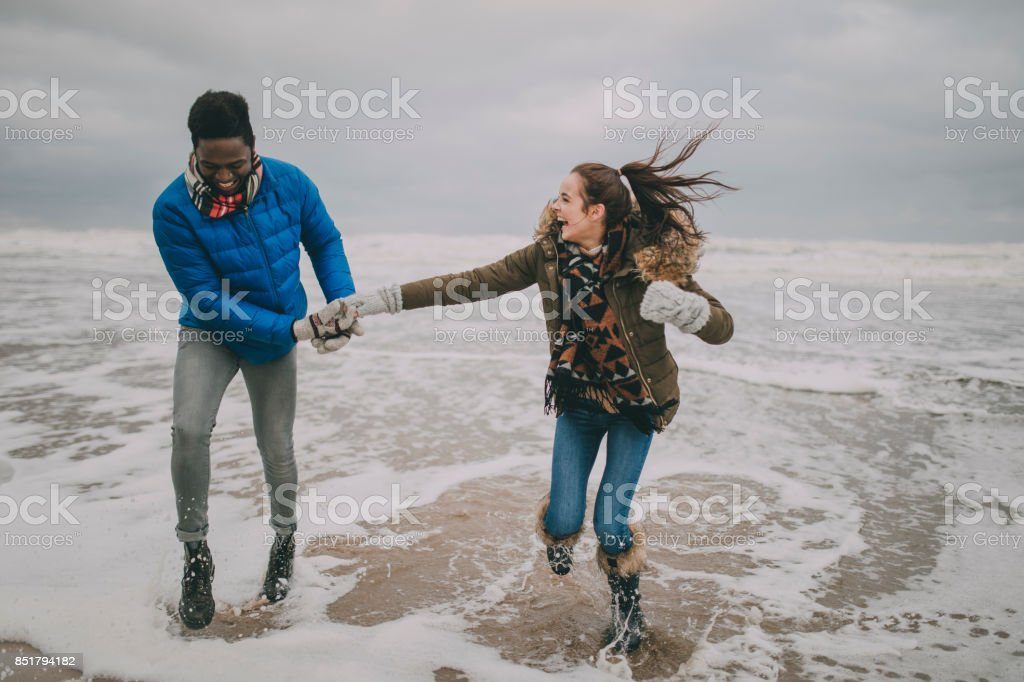 Young Couple Laughing In The Winter Beach Sea foto stock royalty-free