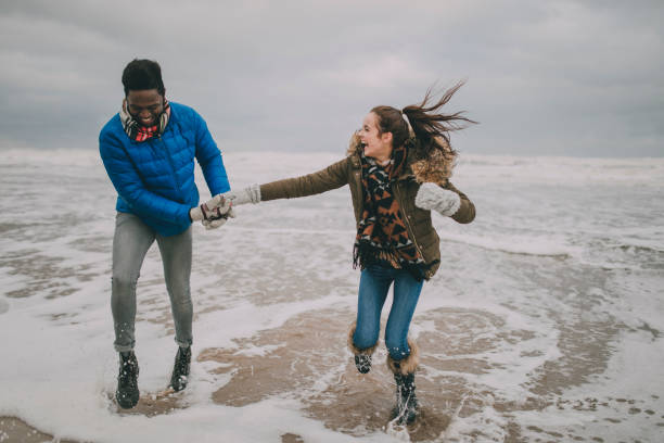 Young Couple Laughing In The Winter Beach Sea stock photo