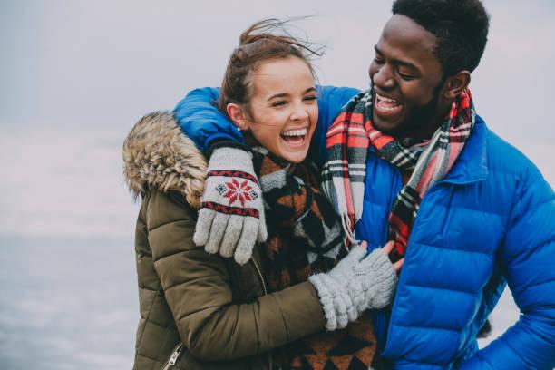 jovem casal rindo numa praia de inverno - viagem ao reino unido - fotografias e filmes do acervo