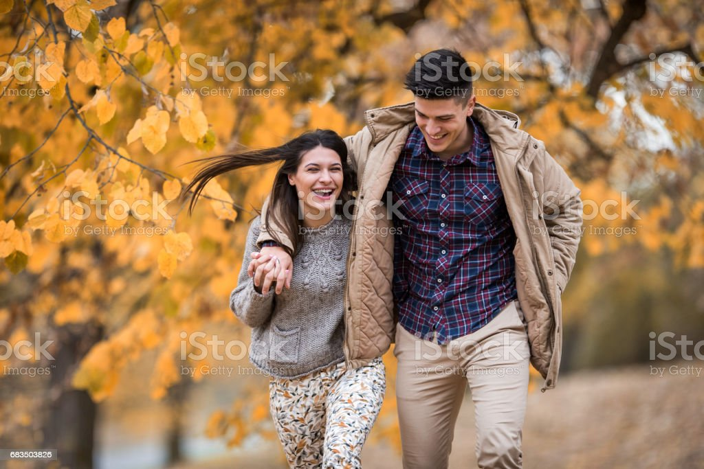 Young couple laughing while running embraced in nature. stock photo