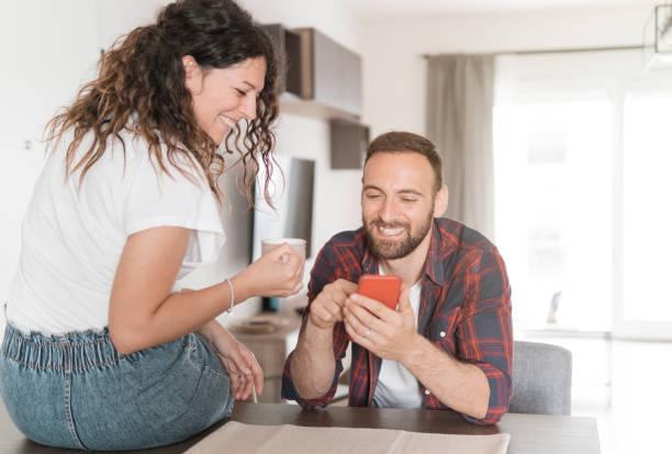 pareja joven se ríe mientras usa el teléfono inteligente - pareja en el amor desayunando juntos y leyendo las últimas noticias utilizando el teléfono móvil - happy couple sharing a cup of coffee fotografías e imágenes de stock