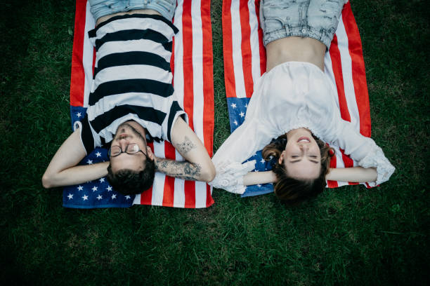 Young couple laying in grass and daydreaming Young couple laying in grass and daydreaming american flag tattoos for men stock pictures, royalty-free photos & images