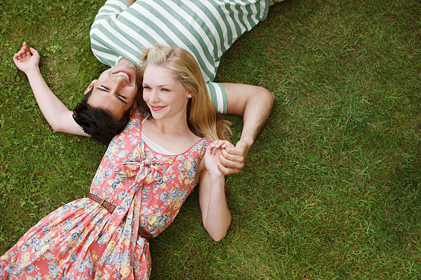 young couple laying in grass and holding hands - falling in love stock pictures, royalty-free photos & images