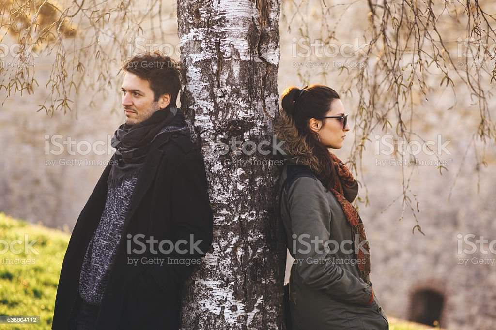 Young couple leaning on a tree in the park stock photo