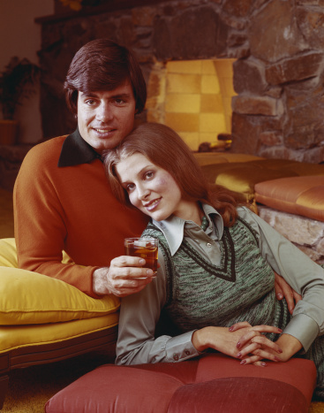 Young couple leaning on cushion with drink near fireplace, smiling