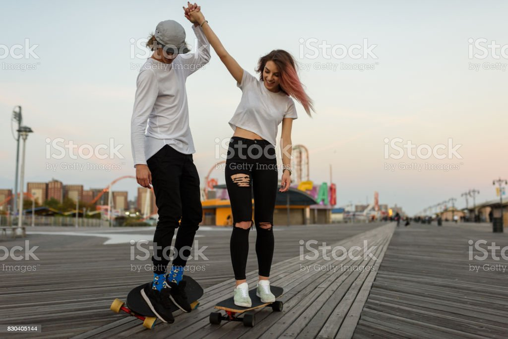 Jovem casal aprender a montar um longboard, de mãos dadas - foto de acervo