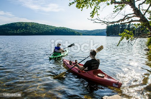 Young couple leaving for a ride in kayak on the lake during summer day