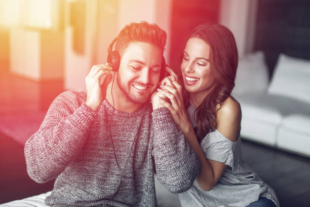 Young couple listening music indoor stock photo