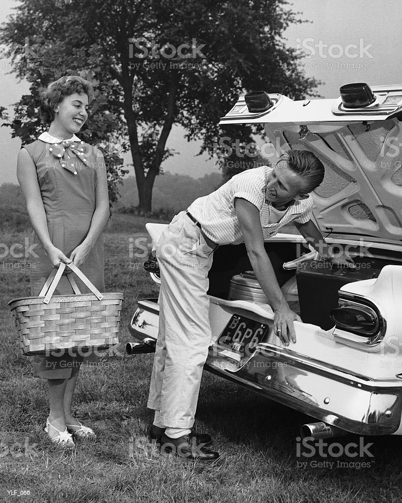 Young couple loading trunk of car for picnic royalty-free stock photo