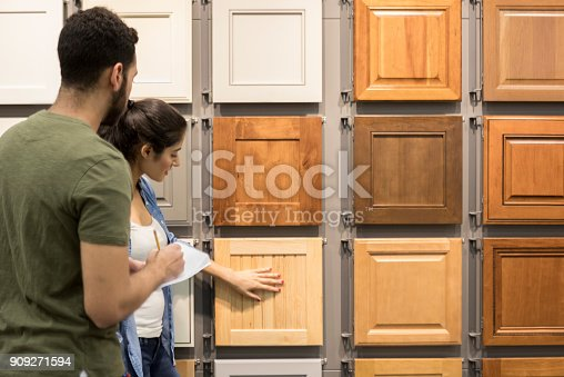 Couple look at cabinet samples in a hardware store. The woman touches one of the cabinet samples. The man is taking notes.
