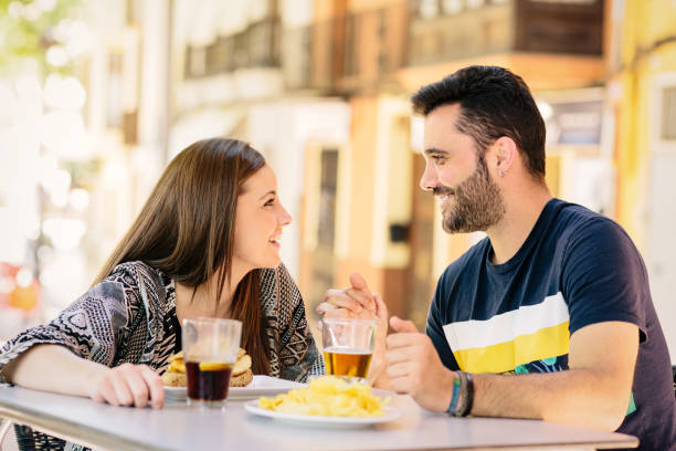 A young couple look at each other on the terrace of a bar while they eat.