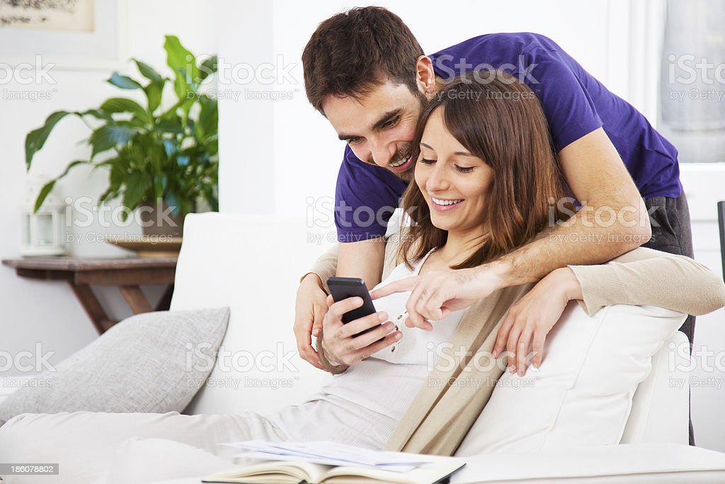 Young couple looking a smartphone at home stock photo