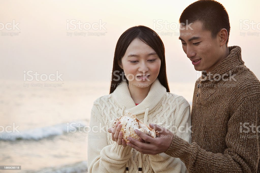Young Couple Looking At a Seashell royalty-free stock photo