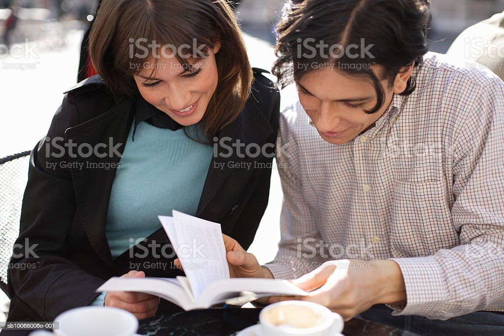 Young couple looking at book at outdoor cafe foto royalty-free
