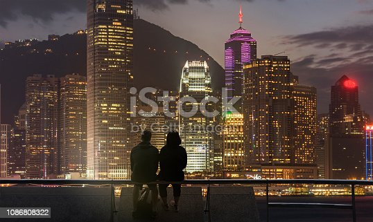 A young couple sitting on a waterfront barrier in the Kowloon district of Hong Kong, looking at the city lights of  Hong Kong Island across the sea channel