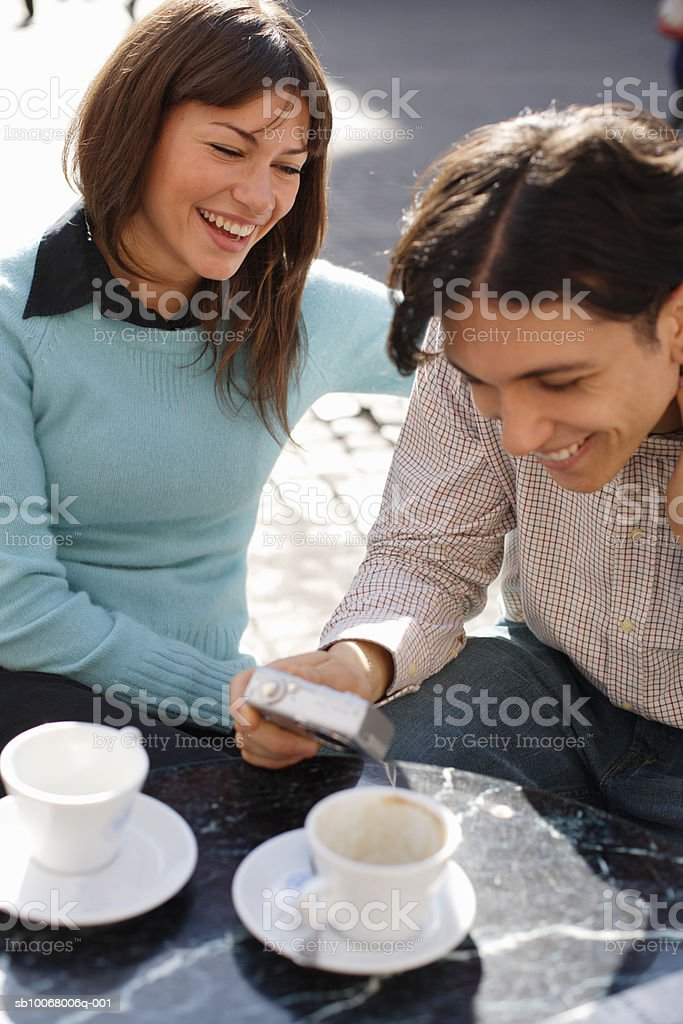 Young couple looking at digital camera at outdoor cafe royalty-free stock photo