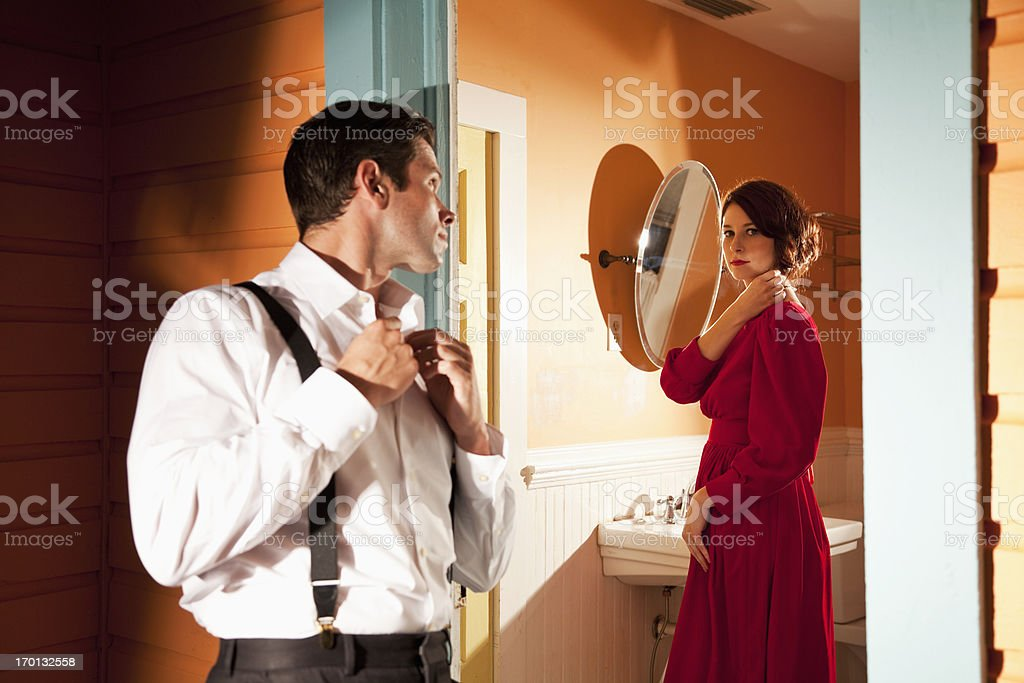 Young couple looking at each other through door stock photo