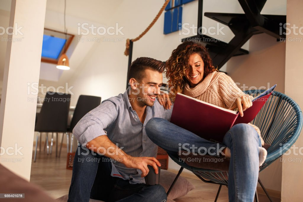 Young couple looking at family photo album.They sitting in living room and drinks coffee. stock photo