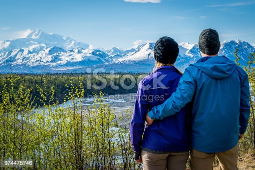 Young couple holding each other and standing in front of mount Denali formerly mount Mckinley, Alaska