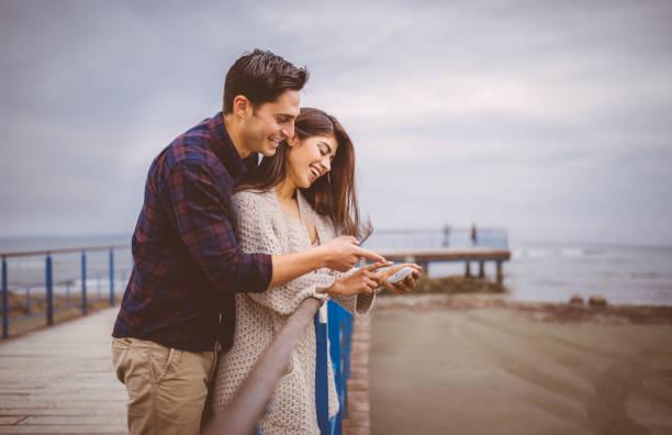 junges paar foto auf smartphone betrachten - hochzeitsreise zypern stock-fotos und bilder