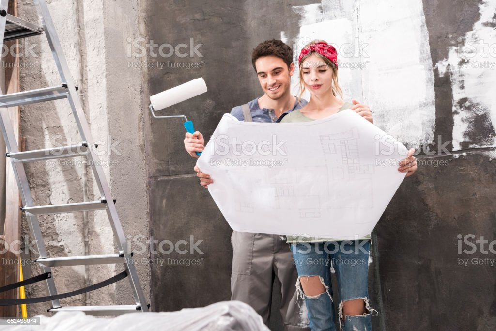 young couple looking at schemes while renovation home royalty-free stock photo