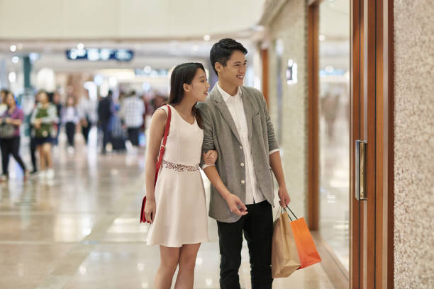Young couple looking at shop window at mall Young couple looking at shop window. Smiling lovers are shopping in luxury mall. They are wearing smart casuals. shopping couple asian stock pictures, royalty-free photos & images