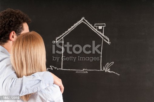 481974106istockphoto Young Couple Looking at Sketched Home 185272319