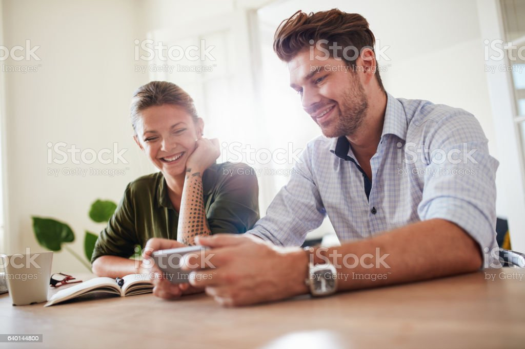 Young couple looking at smart phone and smiling stock photo