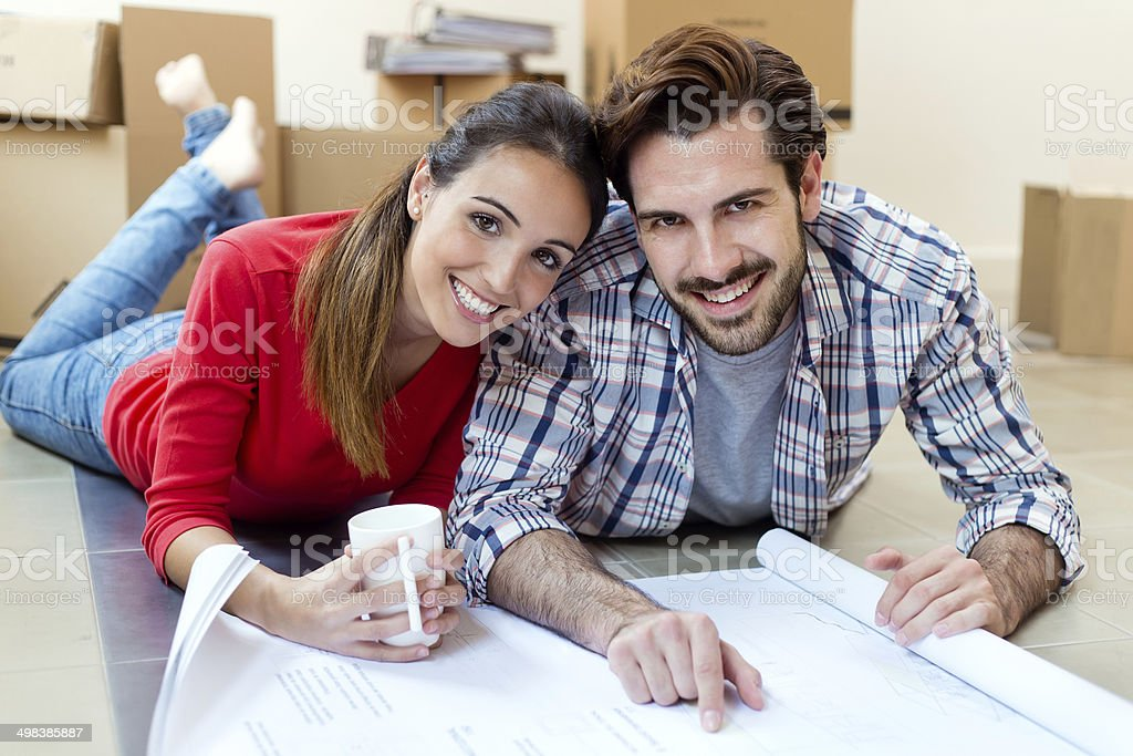 Portrait of Young couple looking at the blueprints of their new home