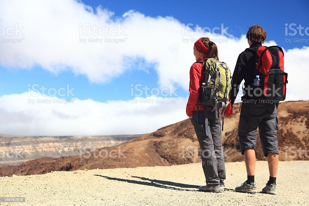 Young couple looking at view while hiking royalty-free stock photo