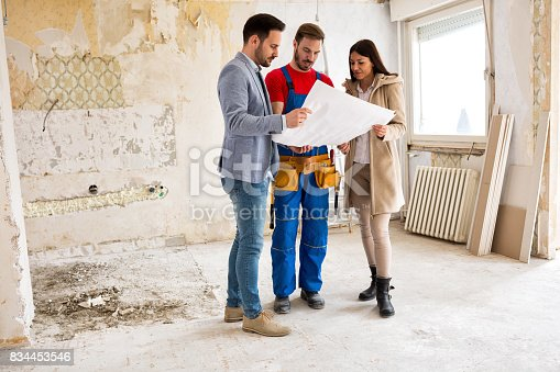 istock Young couple looking blueprints of their home with handyman 834453546