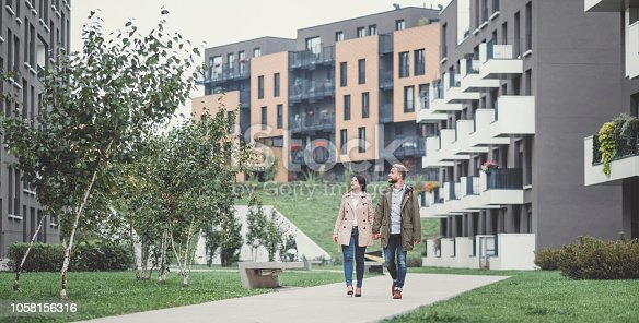 Young couple looking for apartment. Image taken at average residential area with multiple ownership block of flats type of buildings.