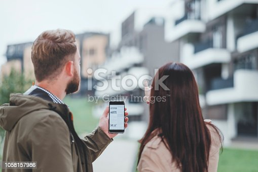 istock Young couple looking for apartment via mobile classified ads 1058157986