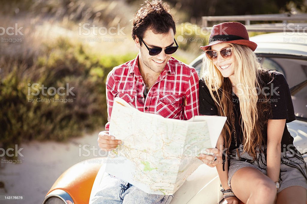 Young Couple Looking For Directions On the Map royalty-free stock photo