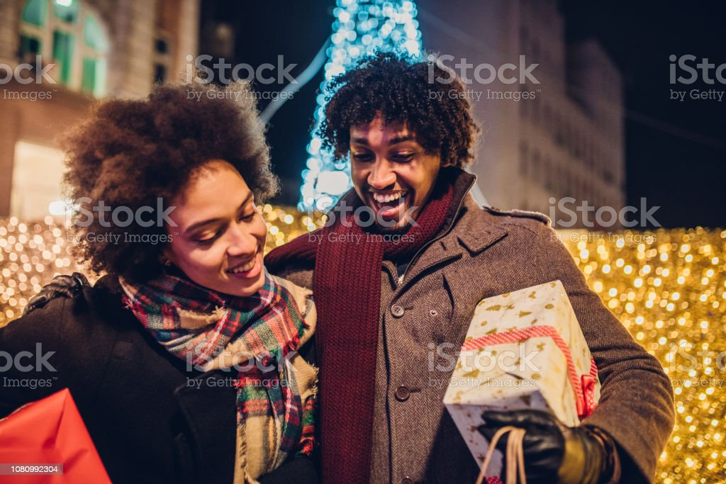 Young couple buying Christmas presents looking inside shopping bag