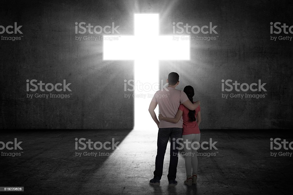 Young couple looking the shining cross on the wall stock photo