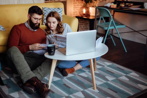 pareja joven busca a través de correo esperando nuevas órdenes - planificación financiera fotografías e imágenes de stock