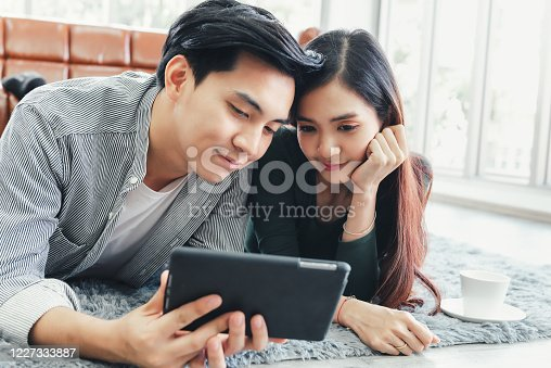 842971872 istock photo Young Couple Love Relax Enjoyment While Online Shopping on Electronic Tablet in Living Room, Portrait of Asian Couple Relaxing on a Couch During Shopping Online Togetherness. Relaxation/ Lifestyle 1227333887