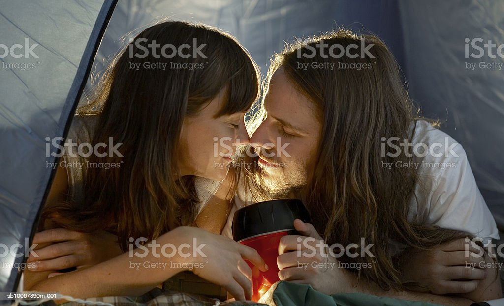 Young couple lying in tent rubbing noses royalty-free stock photo