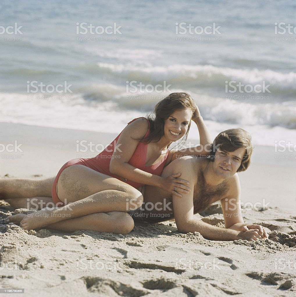 Young couple lying on beach, smiling, portrait stock photo