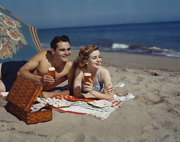 młoda para leżącego na plaży z piwa, uśmiechając się - archiwalny zdjęcia i obrazy z banku zdjęć
