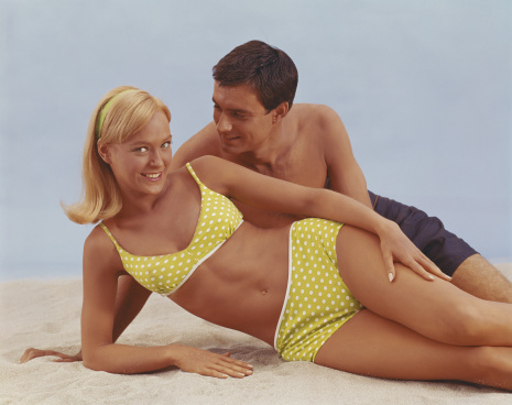Young couple lying on sand, smiling