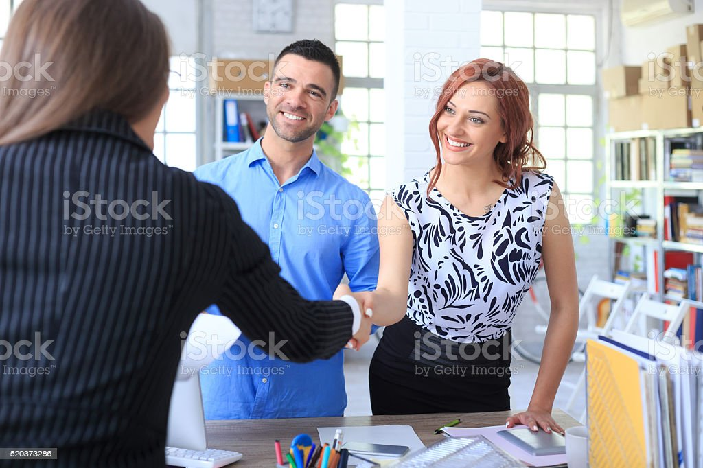 Young couple making a deal with agent stock photo