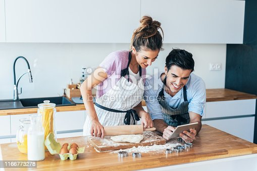 Young couple Looking for a recipe for cookies in the internet using digital tablet