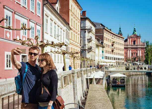 Young couple making selfie Franciscan Church Ljubljanica River Ljubljana Ljubljana, Slovenia - April 29, 2018: Young couple making selfie in front of Franciscan Church of the Annunciation and on the embankment of Ljubljanica River in Ljubljana, Slovenia ljubljanica river stock pictures, royalty-free photos & images