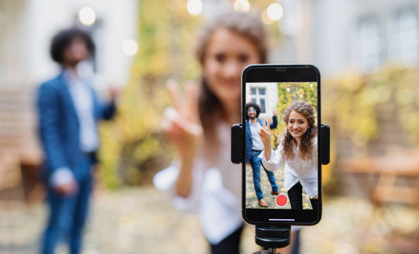 Young couple making video with smartphone outdoors on street, tik tok concept. stock photo